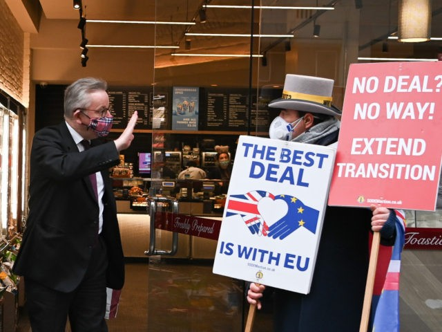 Britain's Chancellor of the Duchy of Lancaster Michael Gove, wearing a face covering due to the COVID-19 pandemic, gestures as he passes anti-Brexit demonstrator Steve Bray whilst exiting a 'Pret a Manger' coffee shop in London on November 30, 2020. - Last-ditch Brexit trade talks continued in London on Sunday …
