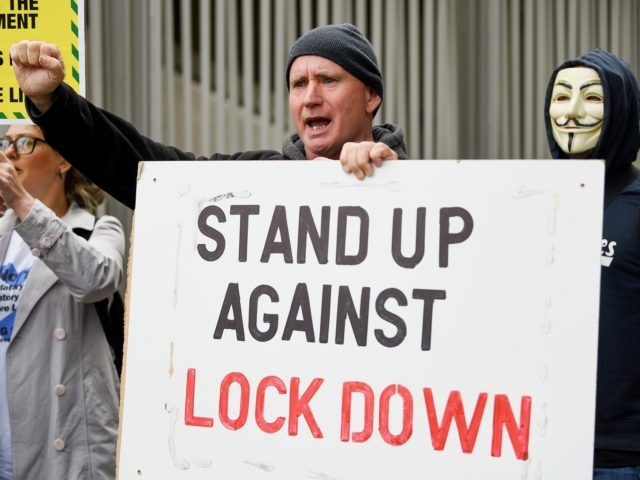 EDINBURGH, SCOTLAND - SEPTEMBER 10: A protester holds a sign that reads 'stand up against lockdown' outside the Scottish Parliament entrance to demonstrate against a secondary lockdown, coronavirus face covering rules and the search for a virus on September 10, 2020 in Edinburgh, Scotland. The group, known as Saving Scotland, …