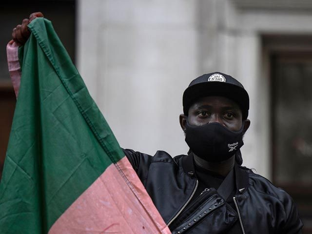 LONDON, ENGLAND - OCTOBER 21: Protesters hold placards and signs calling for the end of police killings of the public in Nigeria, during a demonstration on October 21, 2020 in London, England. Nigerian police opened fire on protestors in Lagos yesterday after 12 days of anti-police demonstrating. Nigerians are protesting …