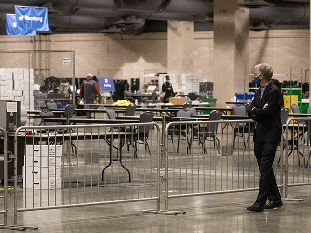 A man watches on from the observers area as election workers count ballots at the Philadelphia Convention Center on November 06, 2020 in Philadelphia, Pennsylvania. Joe Biden took the lead in the vote count in Pennsylvania on Friday morning from President Trump, as mail-in ballots continue to be counted in …