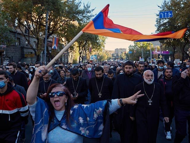 "YEREVAN, ARMENIA - NOVEMBER 11: A woman waves an Armenian flag as protesters march to demand the removal of Armenian Prime Minister Nikol Pashinyan from office near the Armenian parliament building on November 11, 2020 in Yerevan, Armenia. The Russia-brokered deal, which Armenian Prime Minister Nikol Pashinyan called ""incredibly painful …"