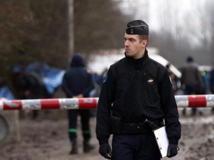 DUNKIRK, FRANCE - JANUARY 06: A police officers stands at the entrance to a new migrant camp on January 6, 2016 in Dunkirk, France. Thousands of migrants continue to live in makeshift camps in the port towns of Calais and Dunkirk in northern France, where they try and board vehicles …