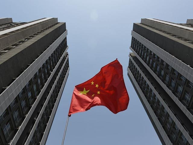 A Chinese flag flies outside a residential compound in Beijing on April 30, 2017. - China has launched perhaps its most concerted push yet to clean up a toxic brew of unregulated and risky lending increasingly viewed as a threat to global financial stability, but do authorities really mean business …