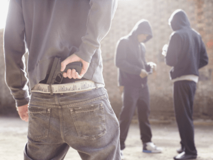 Man with gun robbing drug dealers - stock photo