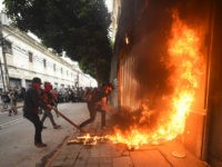 """TOPSHOT - Demonstrators set on fire part of the Congress building during a protest demanding the resignation of Guatemalan President Alejandro Giammattei, in Guatemala City on November 21, 2020. - The Vice President of Guatemala, Guillermo Castillo, asked President Alejandro Giammattei to resign together for """"the good of the country,"""" …"""