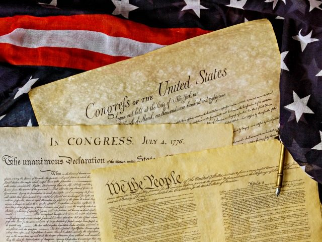 Aged historical documents Washington DC on American Declaration of independence 4th july 1776 on USA flag - stock photo