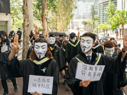 HONG KONG, CHINA - NOVEMBER 19: Students wearing black graduation gowns and Guy Fawkes masks march at the Chinese University of Hong Kong campus as they chant anti-government protest slogans and hold up banners and flags on November 19, 2020 in Hong Kong, China. Chinese University of Hong Kong students …