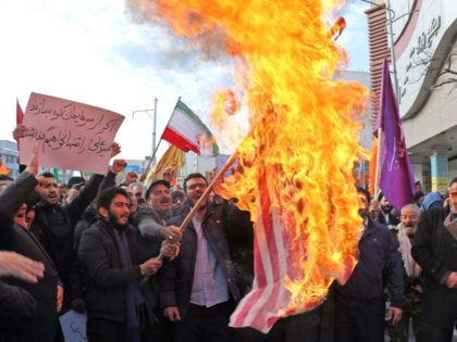 """Iranian men burn a US flag during a protest in support of the Islamic republic's government and supreme leader, Ayatollah Ali Khamenei, in the northwestern city of Ardabil on November 20, 2019, as President Hassan Rouhani said the country's people had defeated an """"enemy conspiracy"""" behind a wave of violent …"""