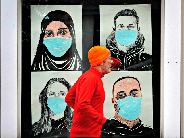 In this Nov. 16, 2020, file photo, a runner passes by a window displaying portraits of people wearing face coverings to help prevent the spread of the coronavirus in Lewiston, Maine. A deadly rise in COVID-19 infections is forcing state and local officials to adjust their blueprints for fighting a …