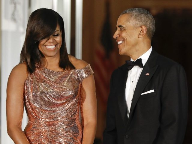 FILE - In this Oct. 18, 2016 file photo, President Barack Obama and first lady Michelle Obama smile on the North Portico for a State Dinner at the White House in Washington. Bare arms and belted waist, a vegetable garden on the White House lawn and parents in the residence: …