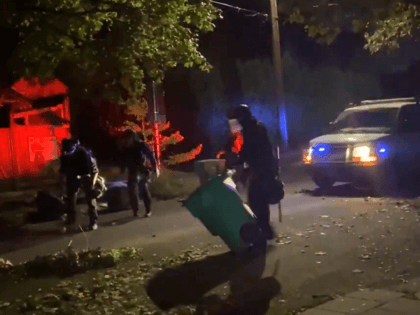 Portland police officers pick up trash cans dumped in street of residential neighborhood Saturday night. (Twitter Video Screenshot)