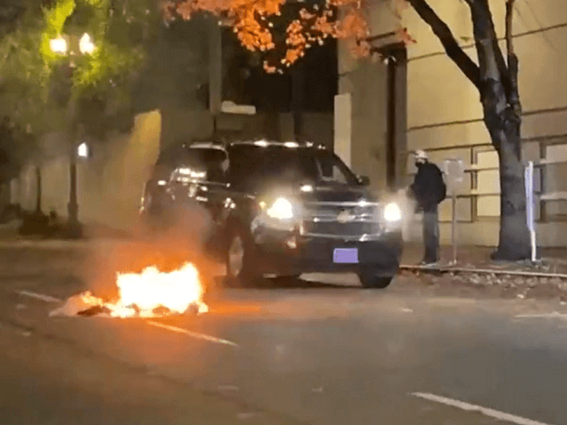 Antifa sets a fire near the Portland Police Bureau central district office. (Twitter Video Screenshot/Andy Ngo)