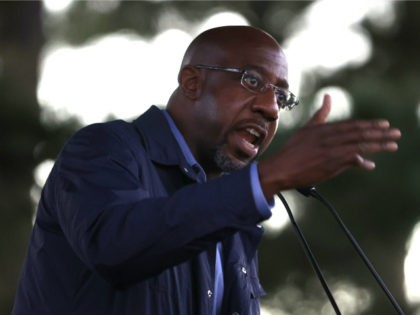 "Democratic U.S. Senate candidate Rev. Raphael Warnock speaks during a ""Get Out the Early Vote"" drive-in campaign event on October 29, 2020 in Columbus, Georgia. With less than a week to go until Election Day, Democratic candidates for the U.S. Senate in Georgia are continuing to campaign throughout the state. …"
