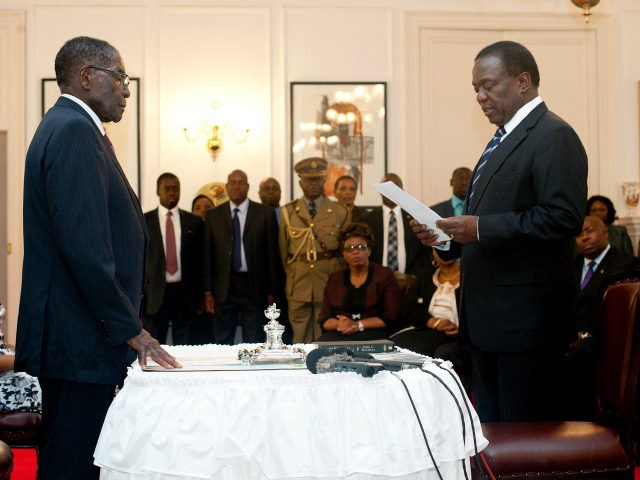 Zimbabwe's newly appointed vice president Emmerson Mnangagwa (R) takes the oath of office before President Robert Mugabe (L) at the State House in Harare on December 12, 2014. Zimbabwe's Justice Minister Emmerson Mnangagwa, a long-time ally of Mugabe, was sworn in as vice president, putting him firmly in line to …
