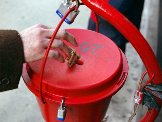 A donation is made into the kettle of Salvation Army bell ringer Robert Walker outside a store on the Magnificent Mile November 21, 2003 in Chicago. Funds raised through the Chicagoland bell ringing campaign will be used year-round to help feed the hungry, shelter the homeless, give help to the …