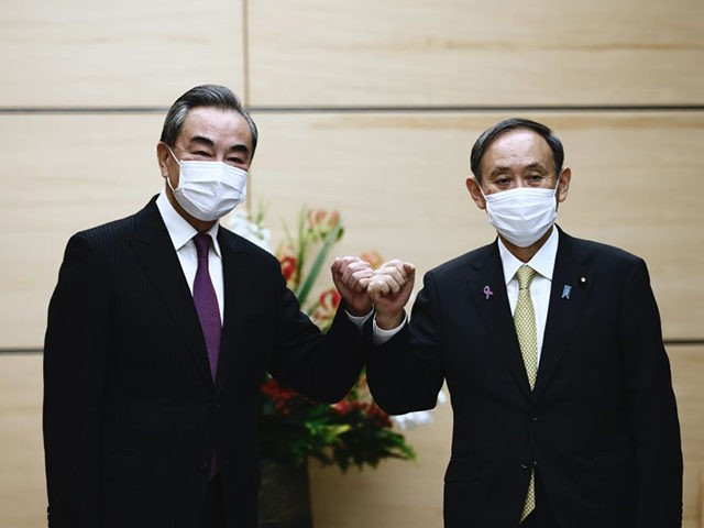 Japans Prime Minister Yoshihide Suga (R) bumps elbows with China's Foreign Minister Wang Yi (L) at the start of their meeting in Tokyo on November 25, 2020. (Photo by Behrouz MEHRI / POOL / AFP) (Photo by BEHROUZ MEHRI/POOL/AFP via Getty Images)