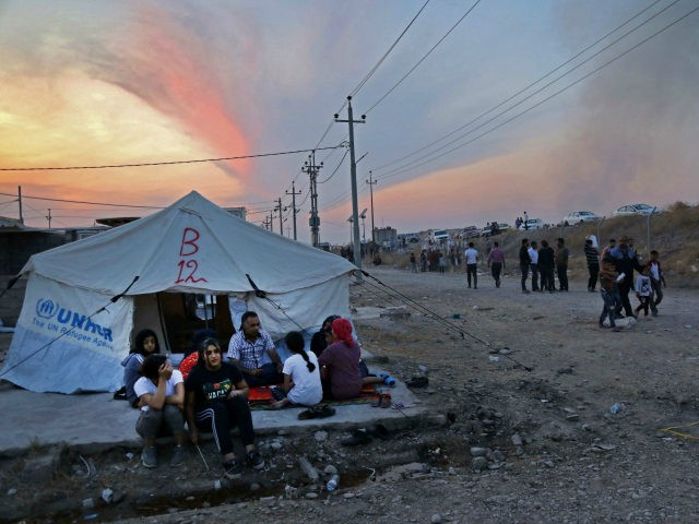 Syrians, who have been recently-turned refugees by the Turkish military operation in northeastern Syria, sit together outside a tent at the Bardarash camp, near the Kurdish city of Dohuk, in Iraq's autonomous Kurdish region, on October 18, 2019. - Over two thousand people, mostly women and children, have fled fighting …