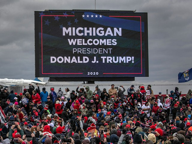 Supporters of U.S. President Donald Trump cheer as Air Force One arrives to a campaign rally at Oakland County International Airport on October 30, 2020 in Waterford, Michigan. With less than a week until Election Day, Trump and his opponent, Democratic presidential nominee Joe Biden, are campaigning across the country. (Photo by John Moore/Getty Images)