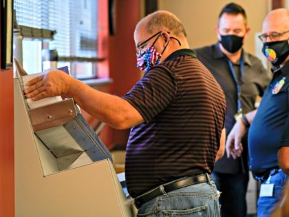 Municipal workers use a machine to open Luzerne County ballots, Wednesday, Nov. 4, 2020, in Wilkes-Barre, Pa. (AP Photo/Mary Altaffer)