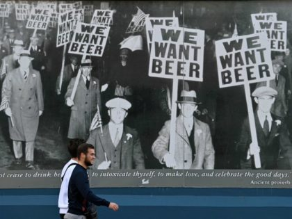 "A pedestrian walks past an image of a 1930s protest against prohibition depicting protestors holding ""We Want Beer"" placards, outside a pub in Liverpool, north west England on October 14, 2020, as new local lockdown measures come in to force to help stem a second wave of the novel coronavirus …"