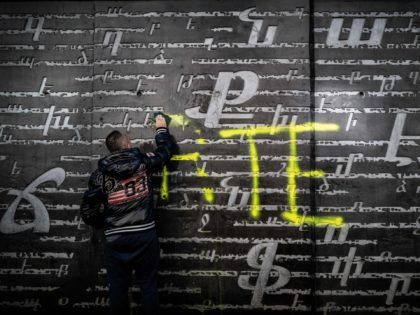 """A man cleans an outside wall of the National Armenian Memorial Centre in Decines-Charpieu, near Lyon, on November 1, 2020 where pro-Turkish yellow letters graffiti tags have been painted overnight. - Inscriptions read """"RTE"""" which can refers to Turkish Prime minister Recep Tayyip Erdogan and """"Grey Wolf"""" (Loup Gris), the …"""