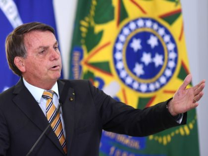 Brazilian President Jair Bolsonaro gestures as he speaks during the launch of a program for the resumption of tourism, a sector severely affected by the new coronavirus outbreak, at Planalto Palace in Brasilia, on November 10, 2020. - Brazil's decision to halt trials of a Chinese-developed Covid-19 vaccine triggered a …