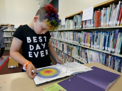 "In this Wednesday, July 12, 2017 photo, Sam, 9, reads a book in the library at Bay Area Rainbow Day Camp in El Cerrito, Calif. The camp caters to transgender and ""gender fluid"" children, aged 4-12, making it one of the only camps of its kind in the world open …"