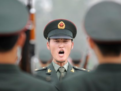 A military officer (C) shouts an order to soldiers of the Guards of Honour of the Three Services of the Chinese People's Liberation Army (PLA) during a training session at a barracks in Beijing on July 21, 2011. The honour guard troops were established in March 1952 and is the …