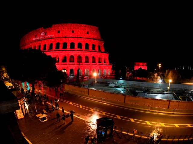 "People gather for a ceremony outside of the Roman Colosseum, illuminated in red light and reading ""Aid to the Church that Suffers,"" drawing attention to the persecution of Christians around the world, particularly in Syria and Iraq, on February 24, 2018 in Rome. / AFP PHOTO / Andreas SOLARO (Photo …"