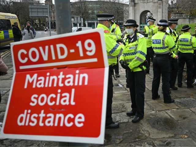 Police officers speak to protester Paul Boys (R) as they attempt to disperse an anti-vax rally and protest against vaccination and government restrictions designed to control or mitigate the spread of the novel coronavirus, including the wearing of masks and lockdowns, in Liverpool, north-west England on November 14, 2020. (Photo …