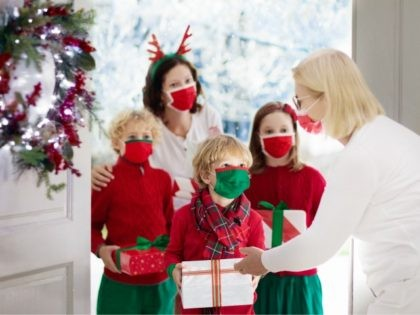 Family with child at grandmother on Christmas day in covid-19 outbreak. Kids in face mask with gifts at home front door. Safe Xmas celebration with grandparents during coronavirus quarantine.
