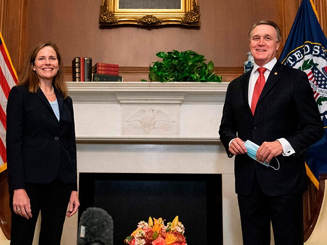 Judge Amy Coney Barrett, President Donald Trumps nominee for Supreme Court, stands for a photo with Senator David Perdue, R-GA at the US Capitol on September 30, 2020, in Washington, DC. (Photo by Manny CENETA / POOL / AFP) (Photo by MANNY CENETA/POOL/AFP via Getty Images)