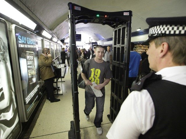 LONDON, ENGLAND - JUNE 02: Police watch as a youth walks through a knife-arch security scanner at Vauxhall railway station on June 2, 2010 in London, England. Over the school half term holiday a range of enforcement and diversionary tactics are being used to keep young people safe in the …
