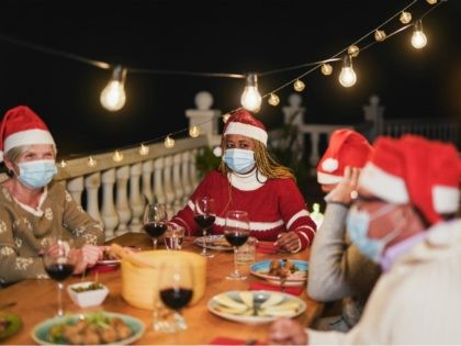 Multiracial senior people celebrate christmas together with dinner outdoor while wearing surgical face mask for coronavirus - stock photo
