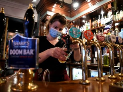 A server wearing a face mask or covering due to the COVID-19 pandemic, pours a pint of Camden Pale Ale inside a pub in Mayfair, London on November 3, 2020, as the country prepares for a second national lockdown during the novel coronavirus COVID-19 pandemic. - English pubs call last …