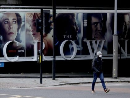 FILE - In this file photo dated Friday, Nov. 20, 2020, a man wearing a face mask walks past a billboard advertising 'The Crown' television series about Britain's Queen Elizabeth II and the royal family, during England's second coronavirus lockdown, in London. Britain's Culture Secretary Oliver Dowden in a newspaper …