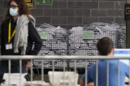 Bins of the empty envelopes from ballots are stored along a wall as election office workers process ballots while counting continues from the general election at the Allegheny County elections returns warehouse in Pittsburgh, Friday, Nov. 6, 2020. (AP Photo/Gene J. Puskar)