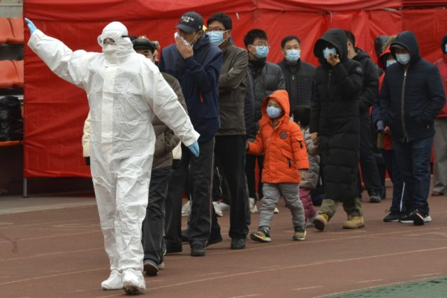 A worker wearing a protective suit gestures to a line of people at a COVID-19 testing site in Tianjin, China, Saturday, Nov. 21, 2020. China is starting mass testing on 3 million people in a section of the northern city of Tianjin and has tested several thousand others in a …