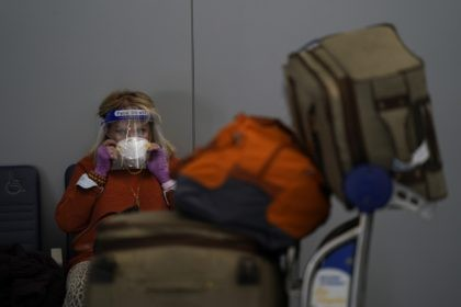 A traveler adjusts her mask while waiting to check in for her flight at the Los Angeles International Airport in Los Angeles, Monday, Nov. 23, 2020. About 1 million Americans a day packed airports and planes over the weekend even as coronavirus deaths surged across the U.S. and public health …