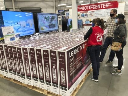 A sales associate helps customers as they consider the purchase of a big-screen television at a Costco warehouse on Wednesday, Nov. 18, 2020, in Sheridan, Colo. U.S. consumer confidence fell to a reading of 96.1 in November as rising coronavirus cases pushed Americans' confidence down to the lowest level since …