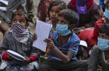 Underprivileged children wearing face masks as a precaution against the coronavirus attend a class at the Sangharsh Vidya Kendra school at a slum area on the outskirts of Jammu, India, Wednesday, Nov.25, 2020. The school provides free education to underprivileged children two days a week. (AP Photo/Channi Anand)