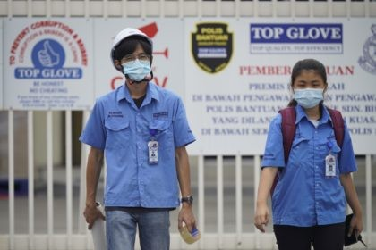 Workers from Top Glove walk out from Top Glove factory in Shah Alam, Malaysia, Wednesday, Nov. 25, 2020. Malaysia's Top Glove Corp., the world's largest maker of rubber gloves, says it expects a two to four-week delay in deliveries after more than 2,000 workers at its factories were infected by …