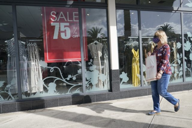 A shopper walks by a store, Monday, Nov. 18, 2020 in Pembroke Pines, Fla. After months of slumping sales and businesses toppling into bankruptcy, Black Friday is offering a small beacon of hope. In normal times, Black Friday is the busiest shopping day of the year, drawing millions of shoppers …