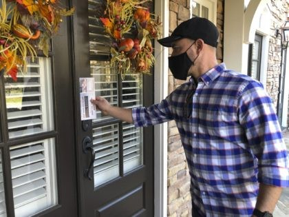 Garrett Bess, vice president of government relations and communications for the conservative activist group Heritage Action For America, leaves information at a residence in a subdivision in Milton, Ga., Friday, Nov. 20, 2020. Bess and a colleague were going door-to-door to encourage people to vote for the conservative candidates in …