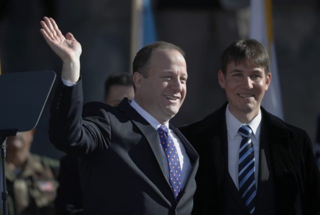 In this Tuesday, Jan. 8, 2019 file photo, Colorado Gov. Jared Polis, left, joins his partner, Marlon Reis, in acknowledging the crowd after Polis took the oath of office during the inauguration ceremony in Denver. Colorado Gov. Jared Polis has tested positive for the coronavirus. Polis and his partner, Marlon …
