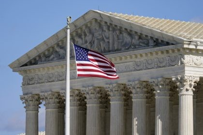 In this Nov. 2, 2020, file photo an American flag waves in front of the Supreme Court building on Capitol Hill in Washington. The Supreme Court is hearing arguments over whether the Trump administration can exclude people in the country illegally from the count used for divvying up congressional seats. …