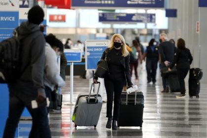 In this Sunday, Nov. 29, 2020 file photo, a traveler wears a mask as she walks through Terminal 3 at O'Hare International Airport in Chicago. The Transportation Security Administration said nearly 1.2 million people went through U.S. airports on Sunday, the highest number since the coronavirus pandemic gripped the country …