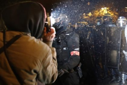 In this Nov.21, 2020 file photo a demonstrator takes a picture of policemen during a protest against bill on police images, in Paris. As videos helped reveal many cases of police brutality, French civil rights activists voiced fears that a new security law would threaten efforts by people from minorities …