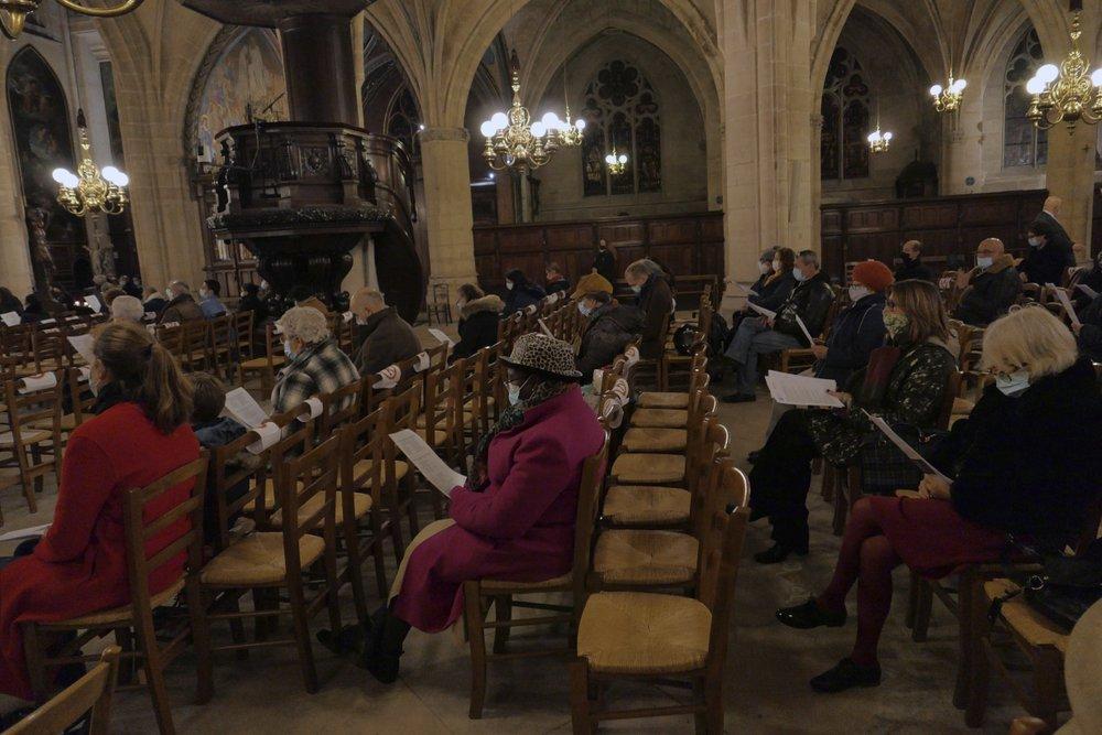 Faithful wearing face masks to protect against coronavirus attend Christmas vespers at the Saint Germain l'Auxerrois church in Paris, Thursday, Dec. 24, 2020, in Paris. (AP Photo/Christophe Ena)