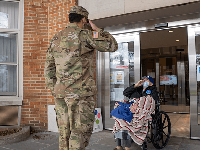 U.S. Army Staff Sgt. Jonathan Pietrantoni, assigned to the 53rd Troop Command, New York Army National Guard, salutes World War II veteran Pfc. Joseph Casaburi on his 99th birthday after he survived a three-month long battle with COVID-19 at the nursing home Angus on Hudson, Hastings-on-Hudson, N.Y., on Dec. 8, …